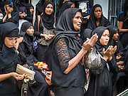 04 NOVEMBER 2014 - YANGON, MYANMAR: Burmese Shia women pray on 32nd Street in Yangon during an Ashura procession. Ashura, commemorates the death of Hussein ibn Ali, the grandson of the Prophet Muhammed, in the 7th century. Hussein ibn Ali is considered by Shia Muslims to be the third imam and the rightful successor of Muhammed. He was killed at the Battle of Karbala in 610 CE on the 10th day of Muharram, the first month of the Islamic calendar. According to Myanmar government statistics, only about 4% of the population is Muslim. Many Muslims have fled Myanmar in recent years because of violence directed against Burmese Muslims by Buddhist nationalists.     PHOTO BY JACK KURTZ