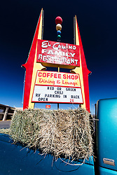 El Camino Family Restaurant sign advertising red or green chiles and truck carrying hay bales. Socorro, New Mexico, USA.