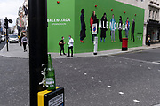 Shoppers beneath the temporary hoarding for Balenciaga, a retail space which is opening soon on Bond Street, on 12th July 2021, in London, England. Balenciaga is a fashion house founded in 1917 by Spanish designer Cristóbal Balenciaga in San Sebastián, Spain.