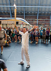 © Licensed to London News Pictures. 26/07/2012. London, UK.  London 2012 Olympics - the Olympic Torch at on its penultimate day (Day 69) of the Olympic Torch Relay at St Pancras International rail station .  Luke Corduner hands the torch over to Danny McCubbin.  Danny holds the torch aloft.  Photo credit : Richard Isaac/LNP