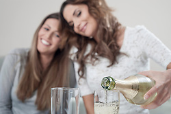 Young woman pouring champage into glasses while her female friend watching
