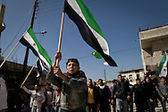 Demonstrators march for regime change, whilst waving the  old Syrian flag as a symbol of protest in the town of Al Janoudiyah, Syria.