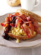 Crispy streaky bacon and scrambled eggs on a bagel with brown sauce