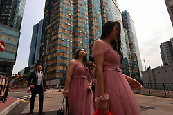 September 30, 2018 - Hong Kong, CHINA - Bridesmaids walk past HARBOURFRONT ONE, a high class residential/commercial complex that suffered dramatic damages to its windows during Super Typhoon Mangkhut hit Hong Kong with a severe wind 2 weeks ago. Mangkhut left scars everywhere in town, many damages still left unattended. Sept-30,2018 Hong Kong.ZUMA/Liau Chung-ren (Credit Image: © Liau Chung-ren/ZUMA Wire)