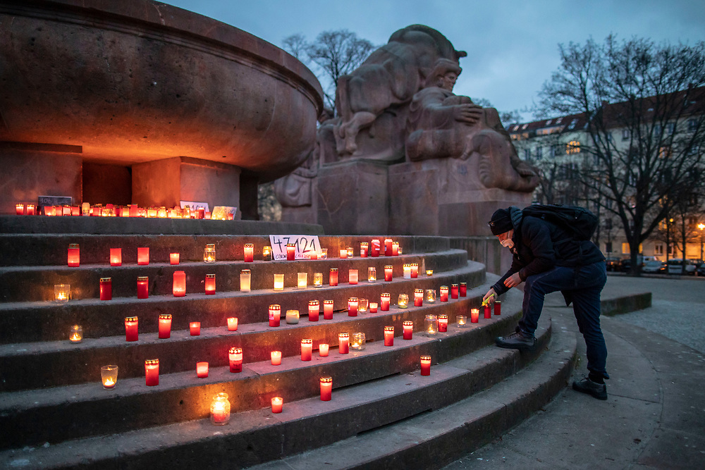 """Christian Y. Schmidt  lights a candle at a makeshift memorial at  Arnswalder Platz in Berlin, Germany, January 17,  2021. The memorial is part of the initiative  """"Corona-Tote sichtbar machen"""" (lit. Make corona deaths visible) by Christian Y. Schmidt and Veronika Radulovic,  since December 6, 2020, people gather at the fountain of Arnswalder Platz every Sunday at 16:00, light candles and place placards with the current death toll reported in Germany at the time. The death toll in Germany by variouse sources revolved around 47,000."""