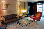 Retro interior design with leather sofa, red leather chair and glass coffee table