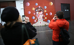 © Licensed to London News Pictures. 11/01/2016. London, UK. People take phone photos of a mural of David Bowie in Brixton. The Death of David Bowie, who was born in Brixton, has been announced today.  Photo credit: Peter Macdiarmid/LNP