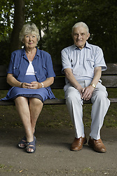 Older couple sitting on a bench in the park and looking at the view,