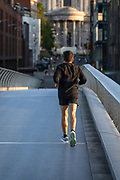 Jogger on Millennium Bridge, with St Paul's Cathedral in background at sunrise, London, England, UK