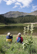 Two hikers rest on hike in mountains of New Mexico.