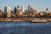 A white NY Waterway boat sails along the East River past buildings of Brooklyn, as seen from Pier 6, Manhattan, New York City, New York, United States of America.