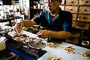 Mixing and weighing herbs at Nguan Choon Tong traditional pharmacy, Phuket Old Town
