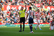 Cristian Gamboa of West Bromwich Albion receives a yellow card from referee Michael Oliver. Barclays Premier League match, Stoke city v West Bromwich Albion at the Britannia stadium in Stoke on Trent, Staffs on Saturday 29th August 2015.<br /> pic by Chris Stading, Andrew Orchard sports photography.