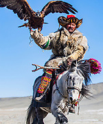 Kazakh eagle hunter riding in the Altai mountains with their golden eagles on horseback, Altai Mountains, Bayan Ulgii, Mongolia