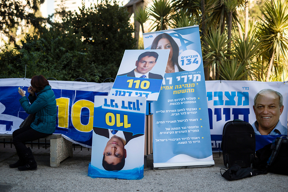 A woman adjusts her makeup as she sits next to campaign posters during the Likud party primary elections, outside a polling station in Jerusalem, on December 31, 2014. Likud's leader and Israel's Prime Minister Netanyahu (not pictured) is widely expected to retain the helm of the right-wing Likud party ahead of Israel's general elections in March.