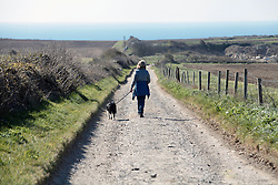 Covid 19 - Woman obeying lockdown rules. Exercising herself and dog down an empty track in Dorset. UK April 2020