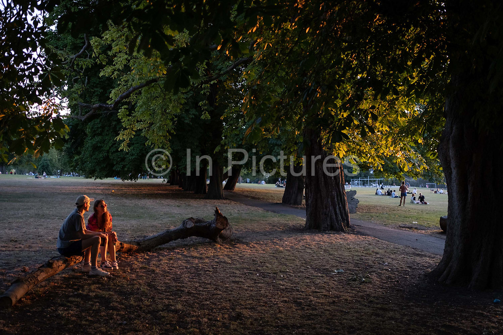 Sitting alongside a grove of horse chestnut trees, a couple enjoy the last warm glow of summer sunlight in Ruskin Park, a public green space in the south London borough of Lambeth, on 6th August 2020, in London, England.