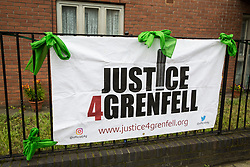 London, UK. 14 June, 2019. A Justice4Grenfell banner and Green for Grenfell scarves close to Grenfell Tower on the second anniversary of the Grenfell Tower fire on 14th June 2017 which claimed the lives of 72 people and injured over 70 more.