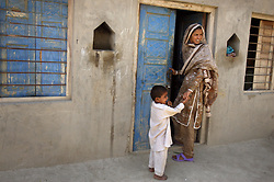 Mukhtar Mai, 33, stands with her nephew, Yaqoub Ahmad, 4, outside her home, which has an outer perimeter guarded by police, Meerwala, Pakistan, April 27, 2005. Mai, has not yet had children of her own, just a marriage that lasted three months. Mai, went against the Pakistani tradition of committing suicide when she brought charges against the men who gang raped her nearly three years ago. With money from the ruling she opened two schools, one for girls, the other for boys. Mai cited that education is the only thing that will stop such acts from happening.