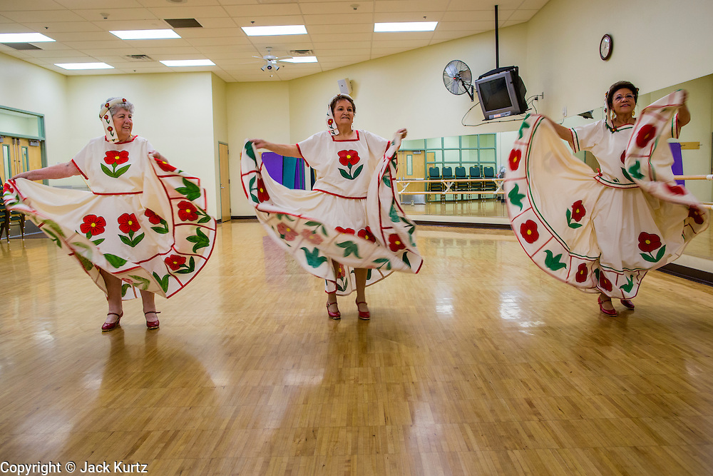 27 JUNE 2012 - GLENDALE, AZ: HELENA ROER, 75 years old, left, HELEN DOWDY, 77, and MARGIE MAY, 65, dance during rehearsal for the Senior Fiesta Dancers at the Glendale Adult Center, in Glendale, AZ, a suburb of Phoenix. Dancing as a part of workout regimen is not unusual, but the Senior Fiesta Dancers use Mexican style folklorico dances for their workouts. The Senior Fiesta Dancers have been performing together for 15 years. They get together every week for rehearsals and perform at nursing homes and retirement centers in the Phoenix area once a month or so. Their energetic Mexican folklorico dances keep them limber and provide a cardio workout.    PHOTO BY JACK KURTZ