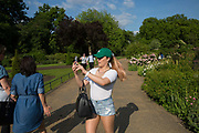 A girl takes photos on her mobiles phone in Hyde Park wild gardens on 24th May 2017 in London, United Kingdom. From the series Our Small World, an observation of our mobile phone obsessions
