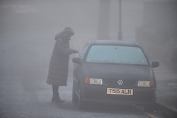 © Licensed to London News Pictures. 11/12/2013<br /> Foggy weather.<br /> A Foggy cold morning as this lady cleans the ice off her car in Pettswood,Kent.<br /> Photo credit :Grant Falvey/LNP