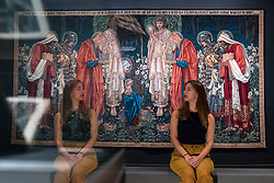 """© Licensed to London News Pictures. 22/10/2018. LONDON, UK. A staff member sits next to """"The Adoration of the Magi"""", 1894, by Edward Burne-Jones.  Preview of the largest Edward Burne-Jones retrospective to be held in a generation at Tate Britain.  Burne-Jones was a pioneer of the symbolist movement and the only Pre-Raphaelite to achieve world-wide recognition in his lifetime.  The exhibition runs 24 October to 24 February 2019.  Photo credit: Stephen Chung/LNP"""