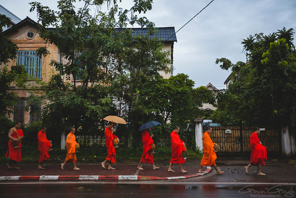 A procession of Buddhist monks in saffron robes walk barefoot past a house on the way to the daily alms-giving, where they will receive rice and money from local people, Vientiane City Centre, Vientiane, Laos