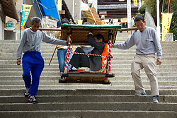 Visitor to Kompira san shrine being carried down 785 steps by porters Shikoku Japan