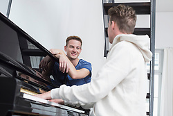 Homosexual couple playing piano, smiling