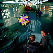 A young man with a Welcome Home balloon, meets his partner after a long absence, in the airport terminal at Chicago-O'Hare airport, Illinois, USA. Waiting for his partner for some hours in the darkened terminal, a late arrival oon this day, the young man has been patient after a slight delay but finally, the girl comes through the arrivals gate to greet her close friend - loving the balloon gesture and pleased to be safely in his arms. Travelling down the escalator into a cross-terminal tunnel they leave the airport for home, 12 months before the terrorist attacks on America that changed the public's attitude to flying on commercial airliners.