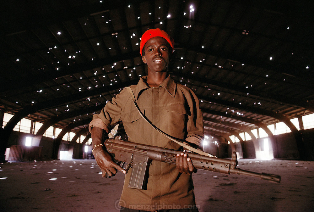 An armed guard in a food warehouse. The port was looted after a firefight the night before, resulting in the deaths of dozens of people. Mogadishu, war-torn capital of Somalia. March 1992.