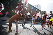 Hackney carnival 2014. The procession started in Ridley Road and passed by the The Hackney Town Hall with thousands of spectators lining the road.<br /> A groupd of dancers dressed in costumes inspired by the cards in Alice in Wonderland.