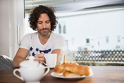 Mid adult man drinking cup of coffee at breakfast table, Munich, Bavaria, Germany