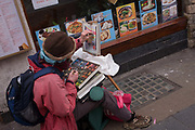 Street artist works outside Chinese restaurant in London's Chinatown. Sitting on a low stool, the artist works colour from crayons onto a canvas, alongside pictures of Chinese food sold in the restaurant on Gerrards Street in Soho, Westminster.