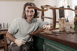 Carpenter repairing an antique wooden chair at workshop, Bavaria, Germany