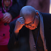 A religious leader joins other members of the public paying their respects at the shrine set up around the towns Christmas tree in Sandy Hook after the mass shootings at Sandy Hook Elementary School, Newtown, Connecticut, USA. 16th December 2012. Photo Tim Clayton