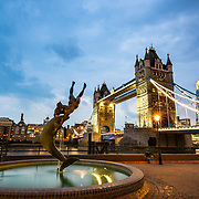 Girl With a Dolphin statue and Tower Bridge at dusk