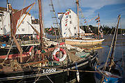 Historic boats on the River Deben by the historic Tide Mill, Woodbridge, Suffolk, England
