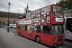 © Licensed to London News Pictures. 11/10/2017. London, UK. Syrian women sing the chimes of Big Ben on a double decker bus in Parliament Square decorated with photographs of their family members missing in the Syrian war. Families for Freedom campaign for the rights of the missing in Syria. Big Ben will miss 200,000 of its bongs, the same number that are are estimated to be in prison in Syria  Photo credit: Peter Macdiarmid/LNP