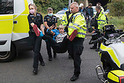 Police officers arrest an Insulate Britain climate activist who had been blocking a slip road from the M25, causing a long tailback on the motorway, as part of a new campaign intended to push the UK government to make significant legislative change to start lowering emissions on 13th September 2021 in Godstone, United Kingdom. The activists, who wrote to Prime Minister Boris Johnson on 13th August, are demanding that the government immediately promises both to fully fund and ensure the insulation of all social housing in Britain by 2025 and to produce within four months a legally binding national plan to fully fund and ensure the full low-energy and low-carbon whole-house retrofit, with no externalised costs, of all homes in Britain by 2030 as part of a just transition to full decarbonisation of all parts of society and the economy.