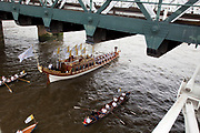 London, UK. Friday 27th July 2012. The London 2012 Olympic Games torch makes it's way up the River Thames on the final day of the torch relay. The pageant, led by the official royal barge, Gloriana was flanked by a flotilla of other rowing boats and vessels. Here passing underneath Hungerford Bridge.