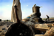 Two boys are feeding a large boiler in an illegal dumping and burning ground located on the banks of the Holy Ganges River near the tannery area of Jajmau, Kanpur, Uttar Pradesh. The scrap leather is destined to be boiled and reduced to a thin dust: the raw material for fertilisers and chicken food production.