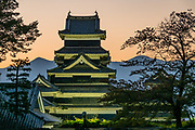 "Lighted east face of Matsumoto Castle, built 1592-1614, backed by twilight over Japan Alps, in Nagano Prefecture. The castle was built from 1592-1614 in Matsumoto. Matsumoto Castle is a ""hirajiro"" - a castle built on plains rather than on a hill or mountain, in Matsumoto. Matsumotojo's main castle keep and its smaller, second donjon were built from 1592 to 1614, well-fortified as peace was not yet fully achieved at the time. In 1635, when military threats had ceased, a third, barely defended turret and another for moon viewing were added to the castle. Interesting features of the castle include steep wooden stairs, openings to drop stones onto invaders, openings for archers, as well as an observation deck at the top, sixth floor of the main keep with views over the Matsumoto city."