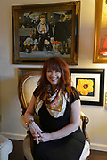 """Sandy Stolberg relaxes in the living room of her condo. On the wall behind her is a print of Edouard Manet's painting, """"A Bar At the Folies-Bergere"""". Photo taken on January 8, 2019 for """"At Home"""" feature on Sandy Stolberg,  who uses dollar store finds as part of the decorations in her Belleville, IL condo.<br /> Photo by Tim Vizer"""