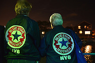 Freeport, New York, USA. September 10, 2014. Two Blue Star Mothers of America members look at the shimmering night lights from houses along the canal while sailing on board the boat Miss Freeport V, which set sail from the Woodcleft Canal of the Freeport Nautical Mile after a dockside remembrance ceremony in honor of victims of the terrorist attacks of September 11 2001, on the eve of the 13th anniversary of the 9/11 attacks. On the back of each jacket is NY6, for the Long Island Blue Star Moms Chapter. Non-political Blue Star Mothers of America gives support for mothers with sons or daughters who are, or were, actively serving in the war.