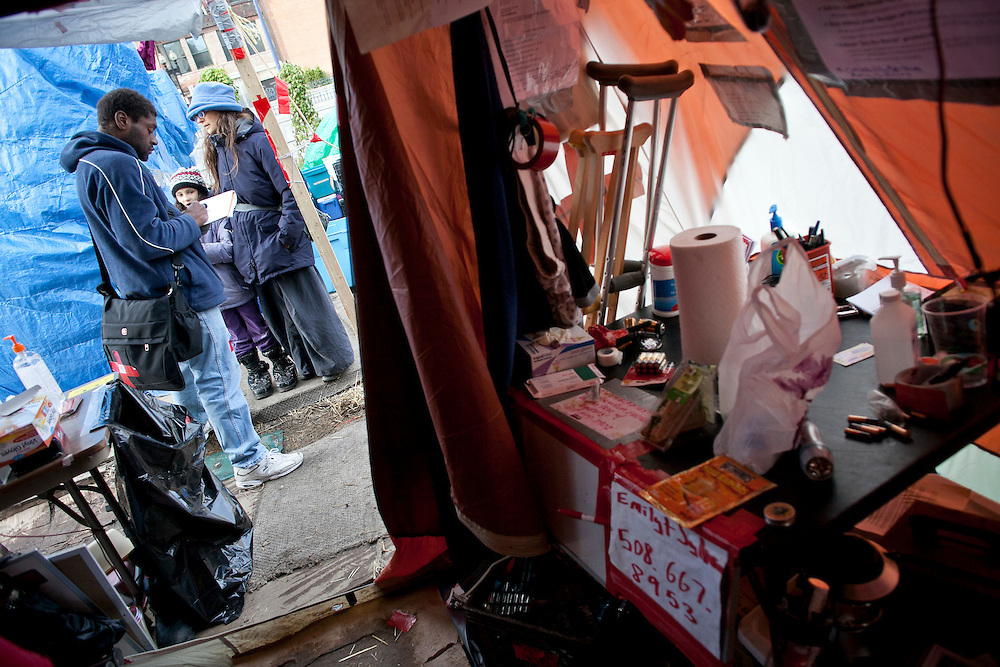 A member of medical team takes care of a girl and her mother as they visit medical tent at Dewey Square in Boston, Massachusetts, October 31, 2011.