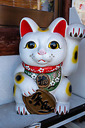 """The maneki-neko, """"beckoning cat"""", is a common Japanese figurine (lucky charm or talisman) which is often believed to bring good luck to the owner. In common interpretation, the left paw raised attracts customers (as displayed in businesses); and/or the right paw raised invites good fortune and money (as displayed at home). Often made of ceramic or plastic, the figurine depicts a cat (traditionally a calico Japanese Bobtail) beckoning with an upright paw, and is usually displayed at the entrance of shops, restaurants, pachinko parlors and other businesses. Some of the sculptures have electric or battery-powered paws. Common colors are white, black, gold and sometimes red. The beckoning cat probably originated in Tokyo (or possibly Kyoto). Earliest records of Maneki-neko appear in the Buko nenpyo's (a chronology of Edo) entry dated 1852. Differing from Western body language, the Japanese beckoning gesture is made by holding up the hand, palm down, and repeatedly folding the fingers down and back, thus explaining the cat's appearance. Photo from Kumano Nachi Taisha shrine, Nachikatsuura, Kii Mountains, Japan."""