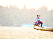 A fisherman sits on a fishing boat in the early morning at Poovar Beach, near Trivandrum (Thiruvananthapuram), Kerala, India