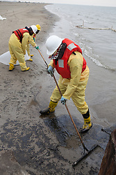 Two relief workers clean up Texas City Oil Spill